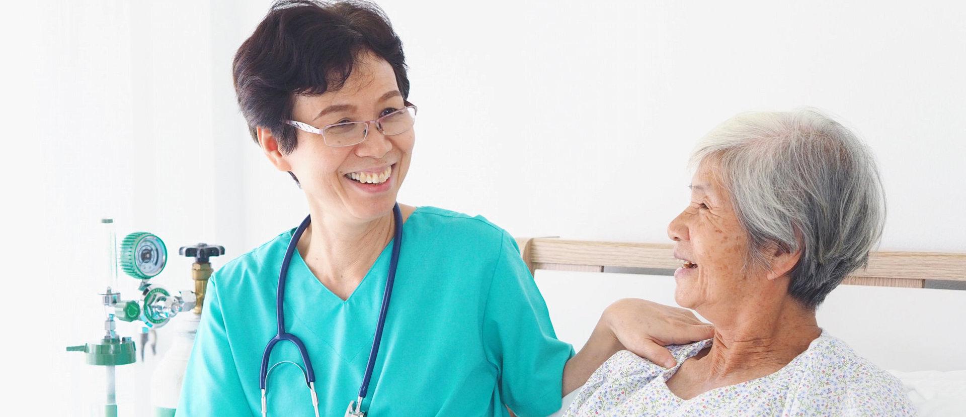Nurse taking care elderly woman in room of hospital