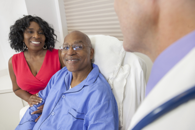 Happy senior man patient recovering in hospital bed with male doctor and wife